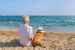 Senior man with dog at the beach