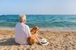Senior man with dog at the beach