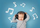 Fototapety little boy on blue blanket background with headphones
