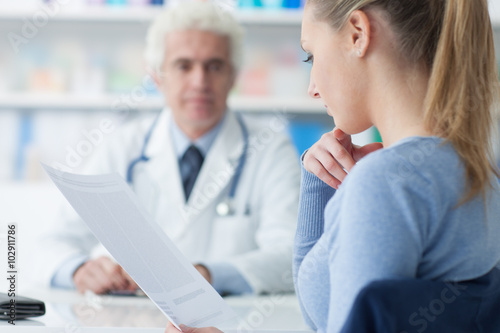 Woman reading medical records плакат