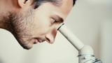 Man lookig through microscope