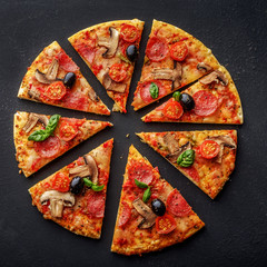 Cut into slices delicious fresh pizza with mushrooms and pepperoni on a dark background. Top view .