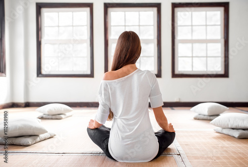 Woman practicing yoga indoors плакат