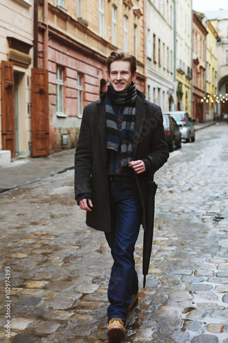"""Street portrait of a young handsome smiling walking man ..."