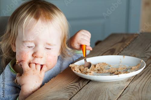 fototapeta na ścianę baby eating porridge at the table