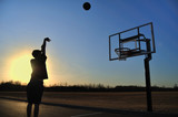Fototapety Silhouette of a Teen Boy shooting a Basketball