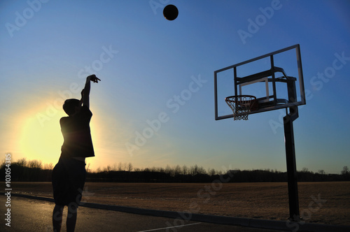 Zdjęcia Silhouette of a Teen Boy shooting a Basketball