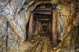 Old abandoned gold ore mine tunnel with wood timbering in Ural