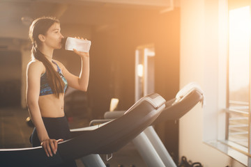 Young woman at treadmill drinking water