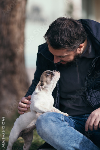 Handsome, bearded, middle age man enjoying outdoors with his adorable French bulldog puppy. City park in background. © tamara83