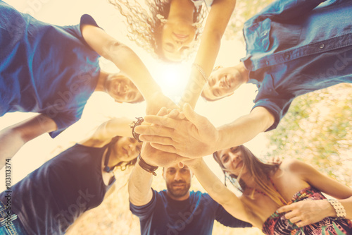 Group of friends with hands on stack and looking down