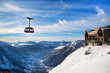 Winter sports travel vacation background. Cable Car tram cabin, lift station, high snow mountain peaks and blue cloudy sky
