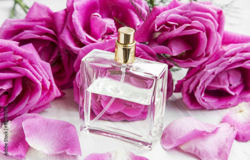 Roses perfume in transparent bottle with pink roses and petals