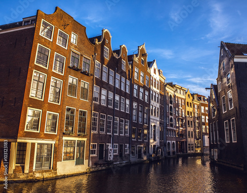 Deurstickers Amsterdam AMSTERDAM, NETHERLANDS - JANUARY 15, 2016: Famous buildings of Amsterdam city centre close-up at sun set time. General landscape view. Amsterdam - Netherlands.