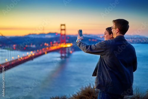 Poster couple taking photo in front of golden gate bridge at sunrise