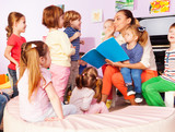 Fototapety Teacher with kids read and discuss book