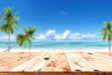 Fototapety Top of wood table with blurred sea and blue sky background - Empty ready for your product display montage. Concept of beach in summer