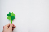 Hand holding paper origami green shamrock on white wall background. Space for copy, lettering, text. St. Patrick