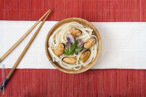 Póster Fideos con mejillones y pulpo en la placa de madera en un makisu roja