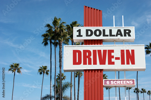 Poster aged and worn vintage photo of drive in sign with palm trees