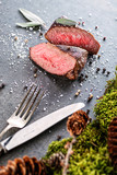 deer or venison steak with ingredients like sea salt, herbs and pepper and cutlery, food background for restaurant or hunting loving