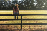 Cowgirl lady woman female wearing cowboy hat and flannel shirt with jeans sitting on country rural fence by a horse pasture paddock looking confident happy serene smart alone waiting watching patient - 103217317