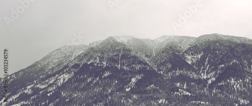 Misty mountain peaks in clouds - 103234579