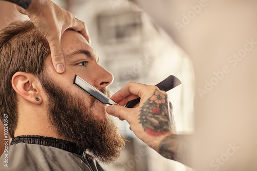 Barber with old-fashioned black razor. Plakat