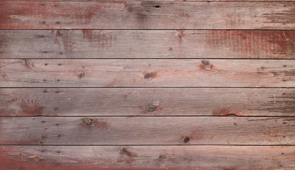 Old red and gray wooden barn door with nails