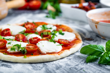 Prepering margherita pizza with mozzarella for baking