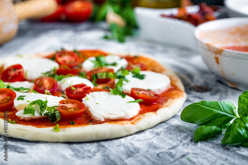 Prepering margherita pizza with mozzarella for baking