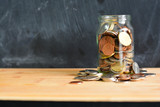 Money or coins in a full jar suggesting home savings