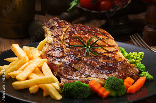 Aluminium Steakhouse Grilled beef steak served with French fries and vegetables on a