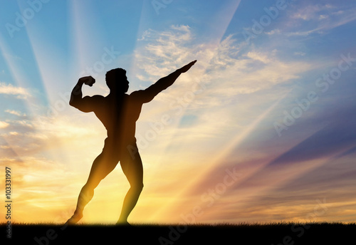 Silhouette of bodybuilder poses at sunset Poster