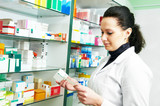 female pharmacist with prescription in drugstore