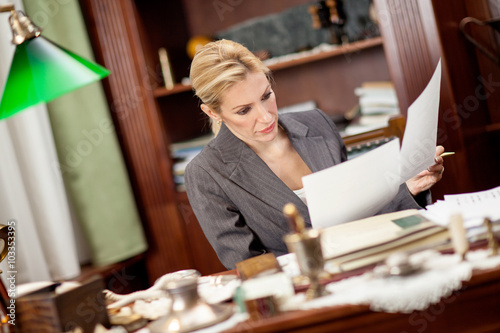 businesswoman sitting at a table in the office and working