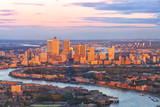 Aerial view of east London financial district of Canary Wharf Docklands circled by Thames river, with buildings illuminated by colourful sunset
