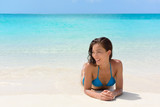 Beach vacation woman relaxing on sand happy. Asian mixed race model looking happy lying down on perfect white sand beach and turquoise ocean water for luxury summer vacations in exotic destination.