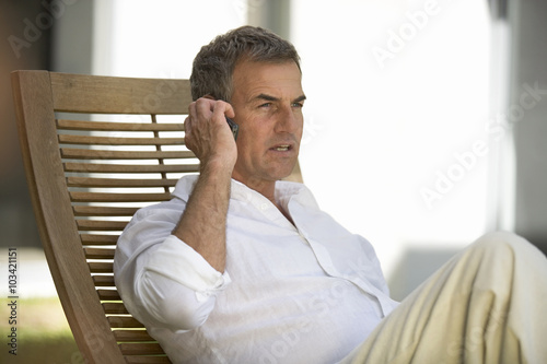 A man sitting on a sun lounger using a mobile phone Poster