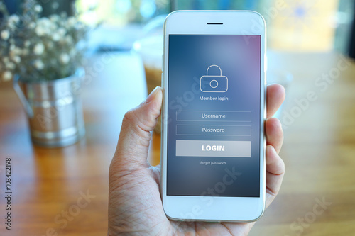 Hand holding smartphone with mebber loging screen