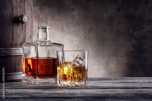 Square decanter and a glass of whiskey with ice Poster