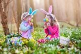 Fototapety Kids on Easter egg hunt in blooming spring garden