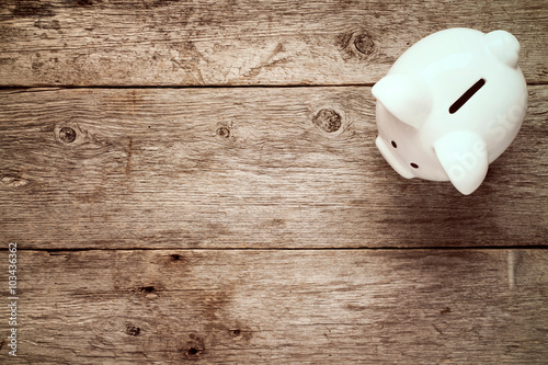 Piggy bank on the old wooden background.