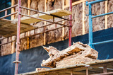 Pieces of glass insulation wool on scaffold against house - 103447790