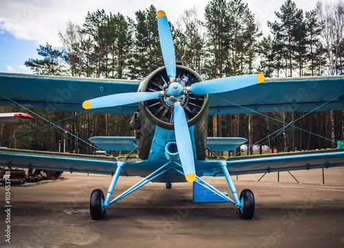 Fototapeta Blue airplane with propeller. Vintage biplane. Front view, with the side of the fuselage. Old retro plane close-up.