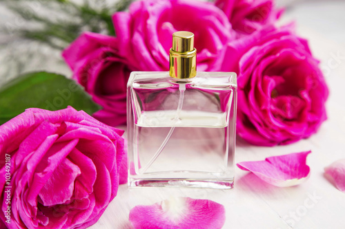 Poster Roses perfume in transparent bottle with pink roses and petals