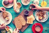 Fototapety Young Happy Family Having Breakfast