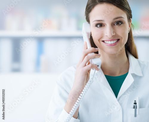 fototapeta na ścianę Smiling doctor phone calling