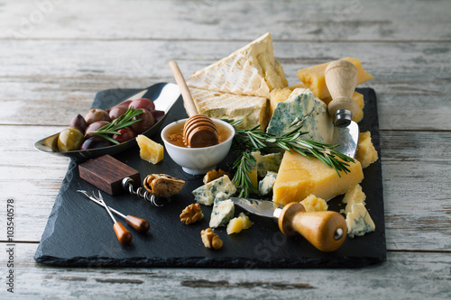 Delicious cheeses on a board with honey, nuts on a white backgro Plakát