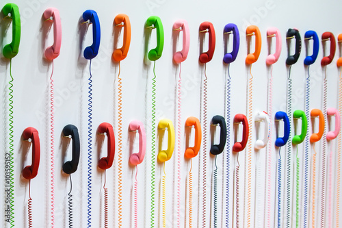 Two rows of colorful handsets are hanging on a white wall. Wires - 103595152